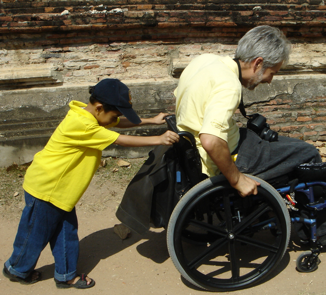 Young boy pushing man in wheelchair