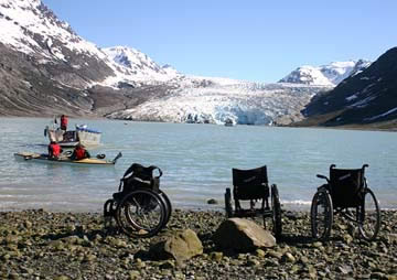 Three empty wheelchairs beside a glacial lake